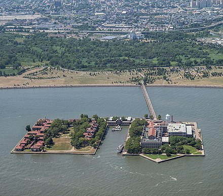 Seen from east. From left to right: contagious diseases ward (island 3); lawn; hospital (island 2); ferry basin; main building, kitchen, dormitory, and immigration building (island 1) Ellis Island Complex.jpg