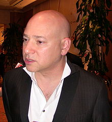 A bald man wearing a white shirt and a black jacket.