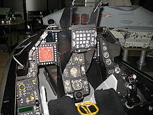Cramped cockpit of jet trainer, showing dials and instruments