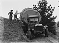 Front on view of a Leyland truck transporting a piece of Kauri along a dirt road (AM 75779-1).jpg