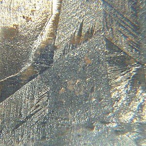 Crystal twinning - Galvanized surface with macroscopic crystalline features. Twin boundaries are visible as striations within each crystallite, most prominently in the bottom-left and top-right.