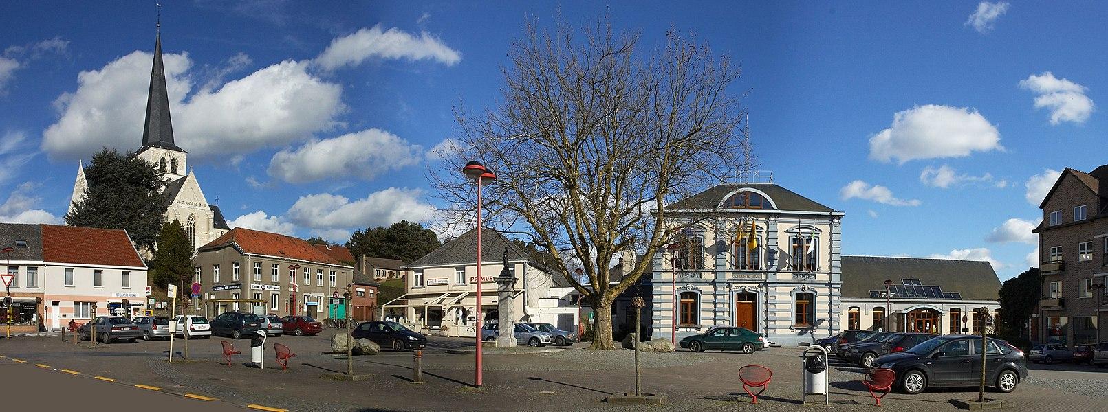 Gemeenteplein Huldenberg met links de kerk, links van de boom (plataan) het standbeeld/pomp en rechts het gemeentehuis. Kijkend richting oost.   Camera location  50°47′21.52″N, 4°34′59.95″E  View this and other nearby images on: OpenStreetMap - Google Earth    50.789311;    4.583319