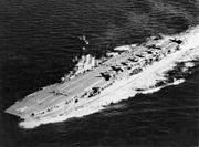 Aerial view of an aircraft carrier travelling at speed. Multiple personnel and aircraft are on the flight deck.