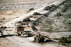 Highway of Death - Aerial view of a destroyed Iraqi column consisting of a T-72 tank, several BMP-1 and Type 63 armored vehicles, and trucks on Highway 8 in March 1991