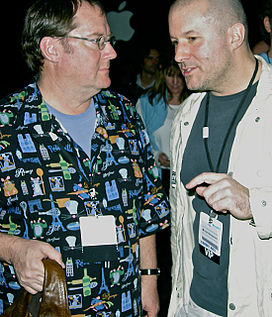 Jonathan Ive is pictured to the right, talking to John Lasseter who is pictured to the left. The Apple logo can be seen in the background.