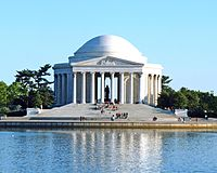 Kulatý bílý památník se sloupy a kopulí před vodou