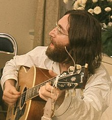 A bearded, bespectacled man in his late twenties, with long black hair and wearing a loose-fitting white shirt, sings and plays an acoustic guitar. White flowers are visible behind and to the right of him.