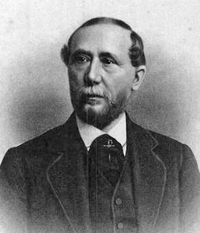 A black-and-white image of a man with thinning hair, mustache and beard wearing a suit and vest, shown from the chest up