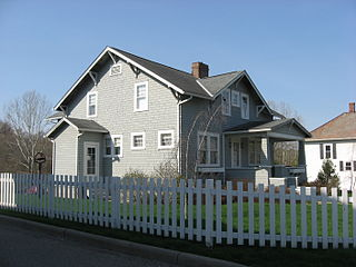 Gray clapboard house, surrounded by a white picket fence