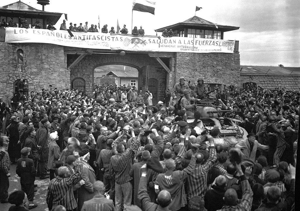 Prisioneros de Mauthausen saludan a la 11ª División Acorazada de los EE UU por su liberación bajo una pancarta escrita en español sobre sábanas