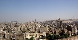 Cairo as seen from the minaret of the Ibn Tulun Mosque.  In the center of the picture the Sultan Hasan Mosque and the Al Rifa'i Mosque, on the right on the hill of the citadel the Muhammad Ali Mosque.