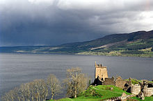 The loch on a cloudy day, with ruins of a castle in the foreground