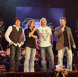 Four middle-aged men standing on a stage in front of an orchestra. Two are holding microphones.