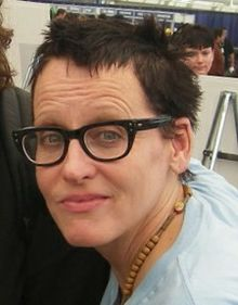 A photograph of a middle-aged woman with short, messy hair, wearing glasses and a light blue T-shirt