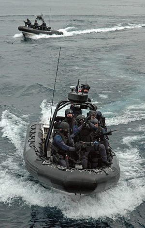 Cutter Boat – Over the Horizon - Maritime Safety and Security Team members aboard an OTH boat. Note the black sponson and M240B machine gun.