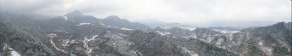 Forested hills covered with snow, seen from an elevated position on Maijishan