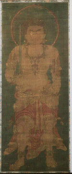 Frontal portrait of a frightening deity dressed only in a skirt-like garment holding a sword in his right hand.