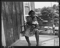Mrs. Aron Conway and baby swinging on porch of their home in company housing project. Adams, Rowe & Norman Inc.... - NARA - 540599.tif