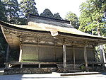 A wooden building with slightly raised floor, a hip-and-gable roof and a canopy over the steps.