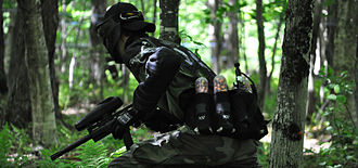 "Paintball - A player taking part in a popular style of paintball known as ""woodsball"""