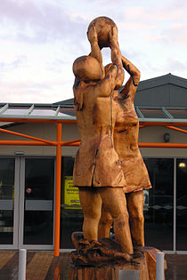 Wooden sculpture of two netball players closely contesting for possession of a netball, at Invercargill Airport in Southland, New Zealand.
