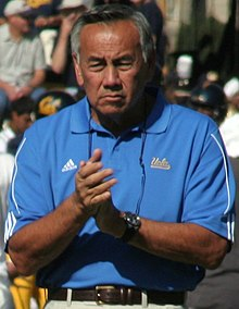 Coach Chow clapping his hands in a blue shirt before a game.