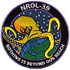 "Mission ""patch"" of NROL-39: an octopus grabbing the earth's globe, labeled ""Nothing is beyond our reach"""