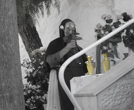 The Way of Humility: Russian Orthodox nun working at Ein Karem, Jerusalem Nun flowers black white.JPG