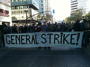 "2011 Oakland general strike - The front of a marching crowd carrying a large banner. The banner reads ""General Strike!"""