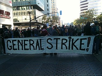 """2011 Oakland general strike - The front of a marching crowd carrying a large banner. The banner reads """"General Strike!"""""""