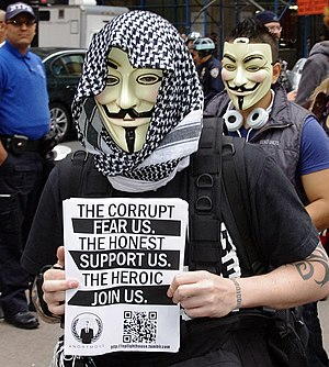 Timeline of events associated with Anonymous - A member holding an Anonymous flier at Occupy Wall Street, a protest that the group actively supported, September 17, 2011