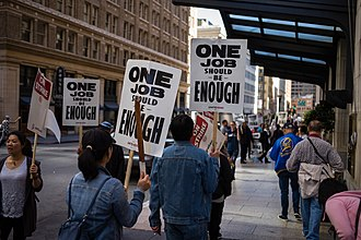 """2018 Marriott Hotels strike - Hotel union workers strike with the slogan """"One job should be enough"""", San Francisco, 2018."""