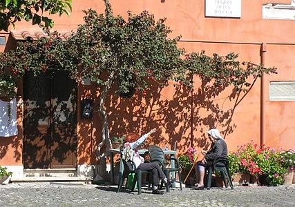 Old ladies enjoying sun under arbor, Ostia Antica, Italy.