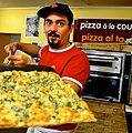Pizzaiolo avec sa pizza à la coupe.jpg