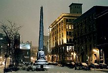 Obelisk and four-story building on winter evening