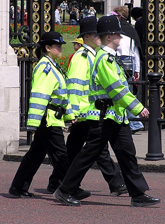 Police community support officer - A PCSO on duty with two police constables. Note the blue epaulettes and cap badge.