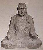 Front view of a cross-legged seated statue with long earlobes. His hands rest on his knees with the palm of his right/left hand turned down/up.
