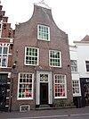 foto van Huis met sobere 18e-eeuwse halsgevel bekroond door gebeeldhouwde kuif; aan de achterzijde trapgevel en uitgebouwde schoorsteen met tandingen. Aan de zijkant getrapgevelde dakkapel. Apothekerswinkel