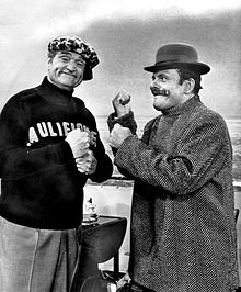 Two men. One the left is Red Skelton, smiling towards the camera. One the right is Terry-Thomas wearing a bowler hat, in a mock boxing stance