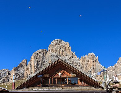 Gable of the the Rifugio Friedrich August, in the background the Langkofel Group with paragliders, Trentino, Italy