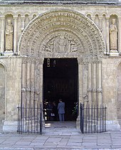 An ancient doorway has sculptured jambs and the figure of Christ within the arch over the lintel.
