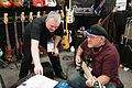 Rod Banach of Regenerate Guitar Works showing Randy George a new bass - 2014 NAMM Show.jpg