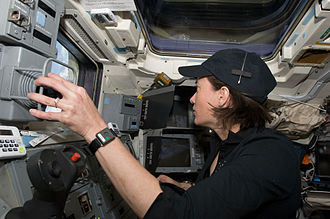 K. Megan McArthur - McArthur, STS-125 mission specialist, works the controls of the remote manipulator system (RMS) on the aft flight deck of the Earth-orbiting Space Shuttle Atlantis during flight day eight activities.