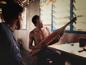 Culture of Sarawak - A Kayan tribesman, playing the Sapeh