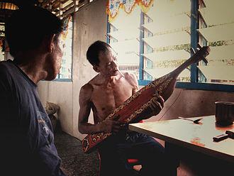 Culture of Sarawak - A Kayan tribesman, playing the Sapeh