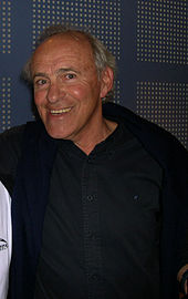 A photograph of a white man with balding grey hair, smiling at the camera while wearing a black buttoned shirt with a blue jacket.