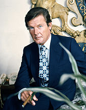 Roger Moore, seated, in a dark blue suit, white shirt and blue and white striped tie with a lighted cigar in his hand on the bed of photographer Allan Warren.  Recording from 1973