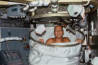 Beta cloth - Conrad in the Skylab shower in 1973 behind the Skylab shower enclosure which was made of Beta cloth stretched between rings.