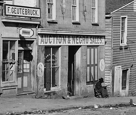 George N. Barnard photograph of Slave trader's business on Whitehall Street Atlanta, Georgia, 1864 ironically shows a United States Colored Troop Infantryman [Corporal] just by the door Slave Market-Atlanta Georgia 1864.jpg