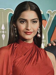 Sonam Kapoor standing in a red dress.